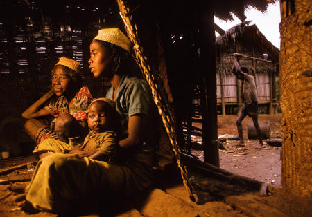A Tanala family sits by the fire, as wood is cut outside, in remote village of Namahoaka in Madagascar.