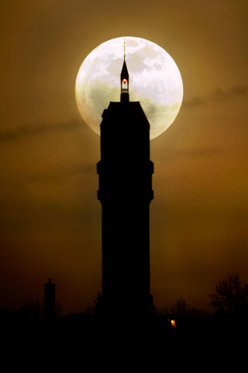 The full moon rises behind Heublein Tower, on Talcott Mountain in Avon, Connecticut.