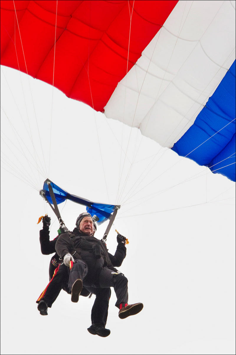 Former President George H. W. Bush rides a tandem skydive to the ground on his 90th birthday.