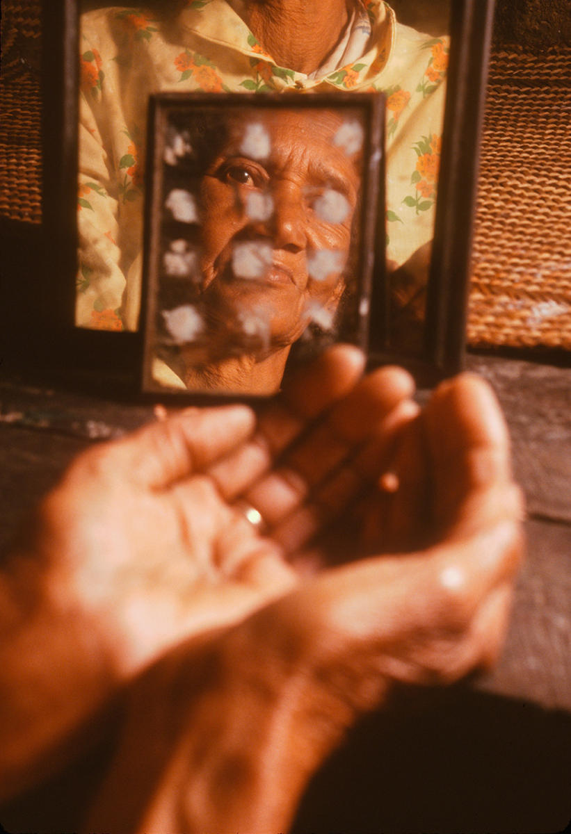 A Malagasy traditional healer looks into a mirror used to communicate with ancestors in the afterlife, to seek their wisdom.