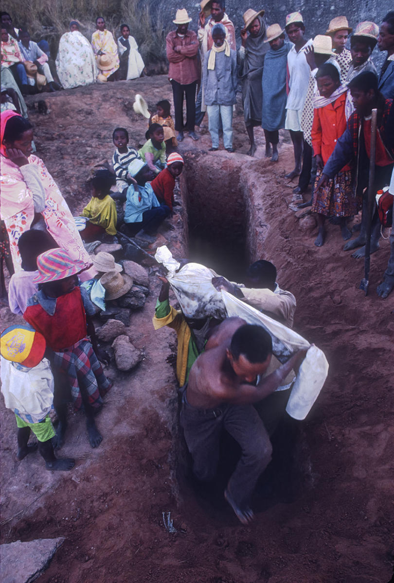 Betsileo villagers carry the remains from the tomb entrance during a Famadihana ritual, which includes exhumation and rewrapping of remains in fresh shrouds. Some Malagasy worship the ancestors, believing all will be well in their lives if they honor and remember the ancestors.