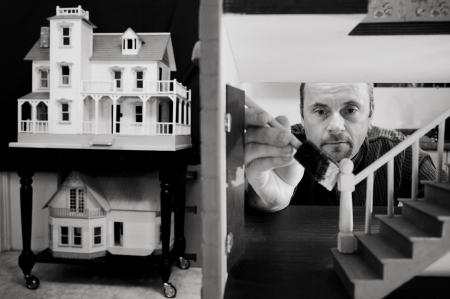 A dollhouse maker puts the finishing touches on his work.