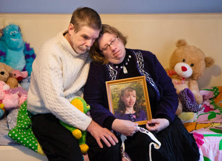 Robert and Susan Meehan sit on their daughter Cyndimae's bed, and hold her photo 24 hours after the medical cannabis patient died unexpectedly.