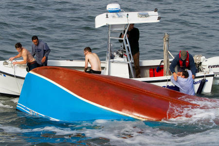The last of of four capsized fishermen, whose boat overturned in rough surf between the Well Beach and Drakes Island breakwater, is rescued by the Wells Harbor Master crew.
