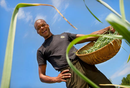 Maine legislator, Farmer and fierce advocate for Maine's sustainability movement,  Craig Hickman smiles while picking garlic scapes on his Annabessacook Farm in Winthrop.