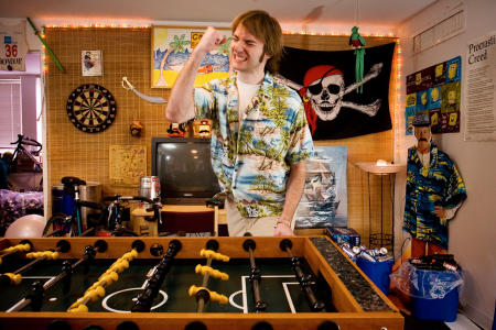 A Bowdoin College student celebrates a score while playing foosball in his dorm room. (Shot for US News & World Report Best Colleges Guide)
