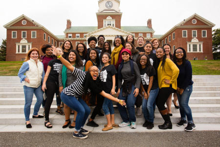 Colby College Alumni of Color Network members pose for a group portrait on the Miller Library steps during Homecoming Weekend on the Waterville, Maine Campus. (Shot for Colby College)