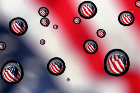 Images of Old Glory are refracted through tiny raindrops on a car's windshield.
