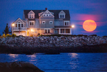 The full moon rises over South Point, Biddeford Pool on the Maine Coast.