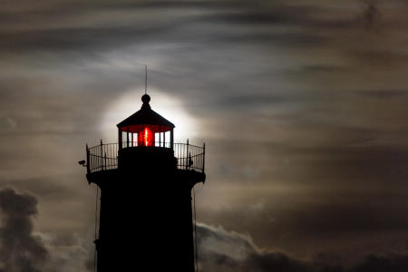 The Harvest Moon rises behind the beacon of Nubble Light in Cape Neddick, Maine.