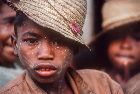 A Betsileo youth fresh from the rice paddies, has dried mud speckles on his face in remote Ambozatany.