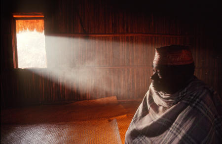 Namahoaka village leader, or Mpanzaka, Zafy Romain sits inside the Trano Be, or Big House, as smoke highlighted by morning light emerges through the window.